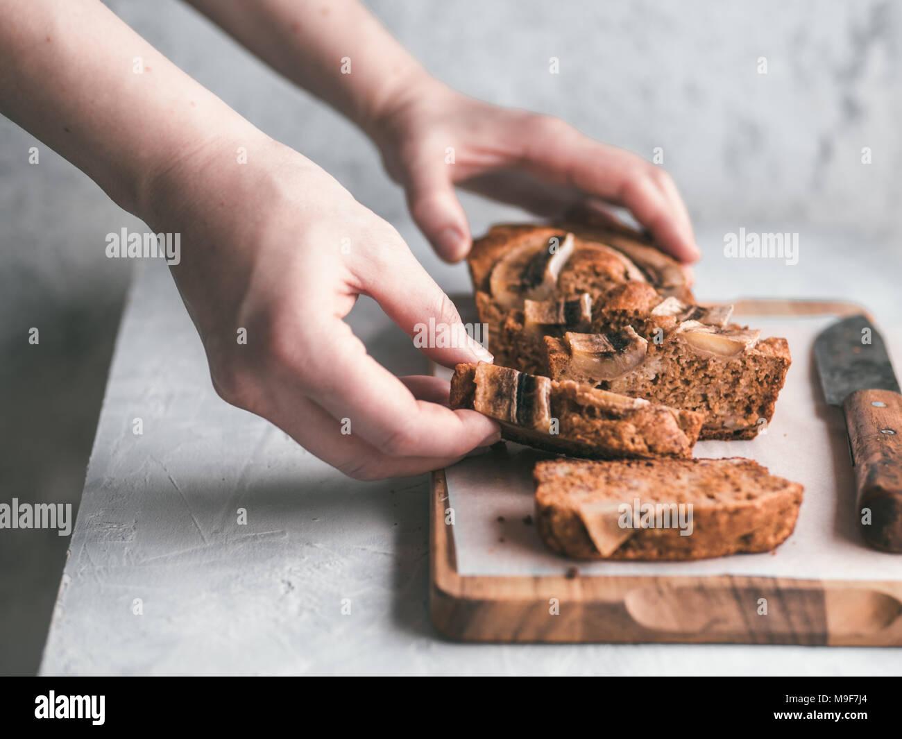 Butter, Zucker-freien Bananenbrot mit Hafermehl, weiche Quark, Honig. Frau hand mit Scheibe Bananenbrot auf grau Tabelle. Ideen Rezept gesunde Ernährung Frühstück. Selektiver Fokus Stockbild