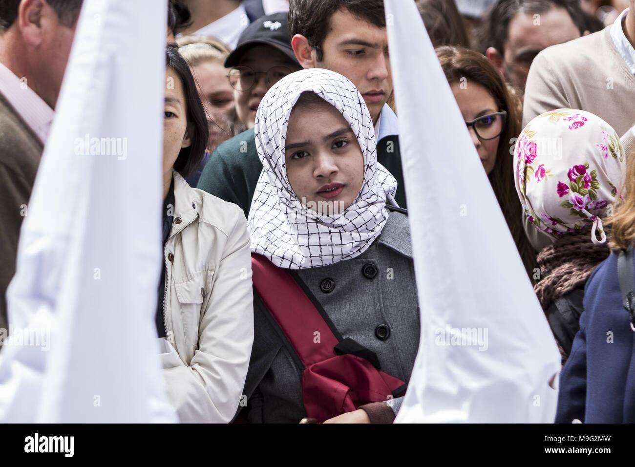 Sevilla, Spanien. 25 Mär, 2018. Ein muslimisches Mädchen nimmt die Prozession der Bruderschaft namens ''La Borriquita'' während der Parade zu Kathedrale am Palmsonntag, Tag namens Domingo de Ramos in Spanisch. Credit: Daniel Gonzalez Acuna/ZUMA Draht/Alamy leben Nachrichten Stockfoto