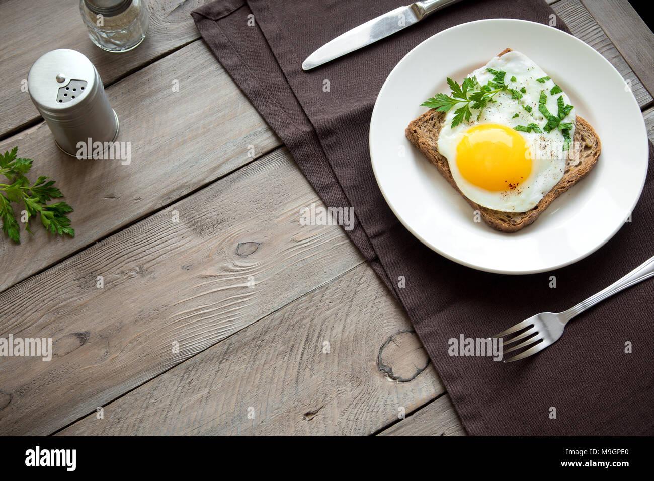 Spiegelei auf Vollkorn Toast und Kaffee zum Frühstück. Spiegelei mit Brot auf dem Teller über Holz- Tabelle, Ansicht von oben, kopieren. Stockbild