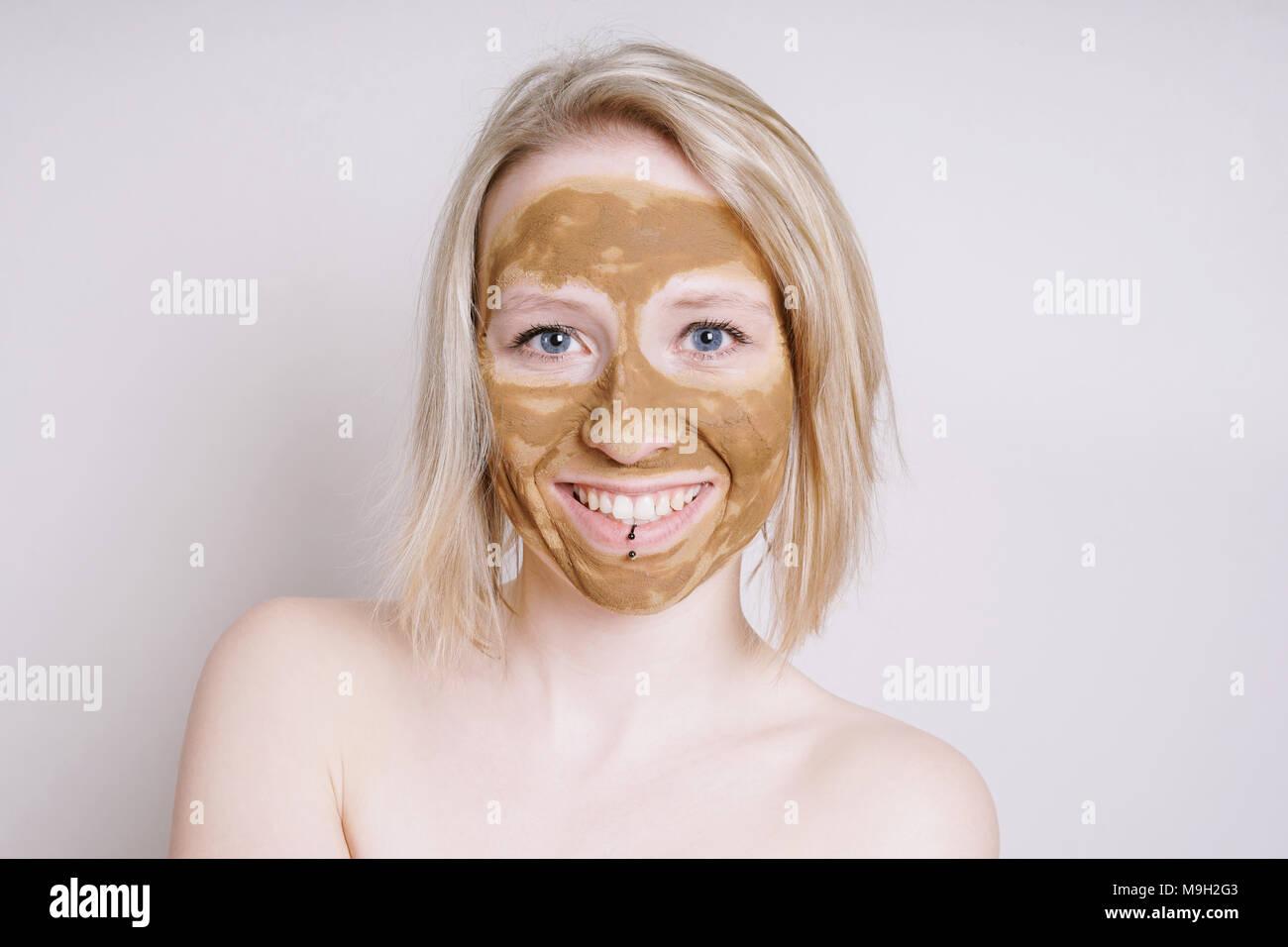 Junge Frau mit der Heilung der Erde oder Lehm beauty Gesichtsmaske Stockbild