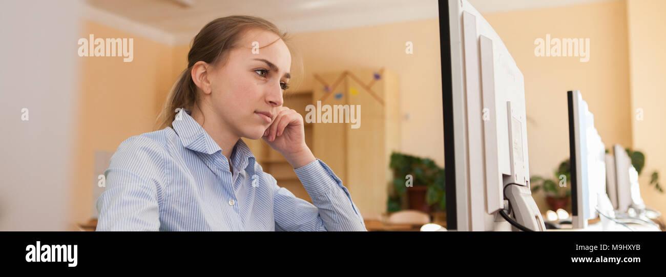 Konzentriert, Geschäftsfrau, die versuchen, eine schwierige Aufgabe auf Linie in einem Desktop-Computer im Büro zu lösen Stockbild