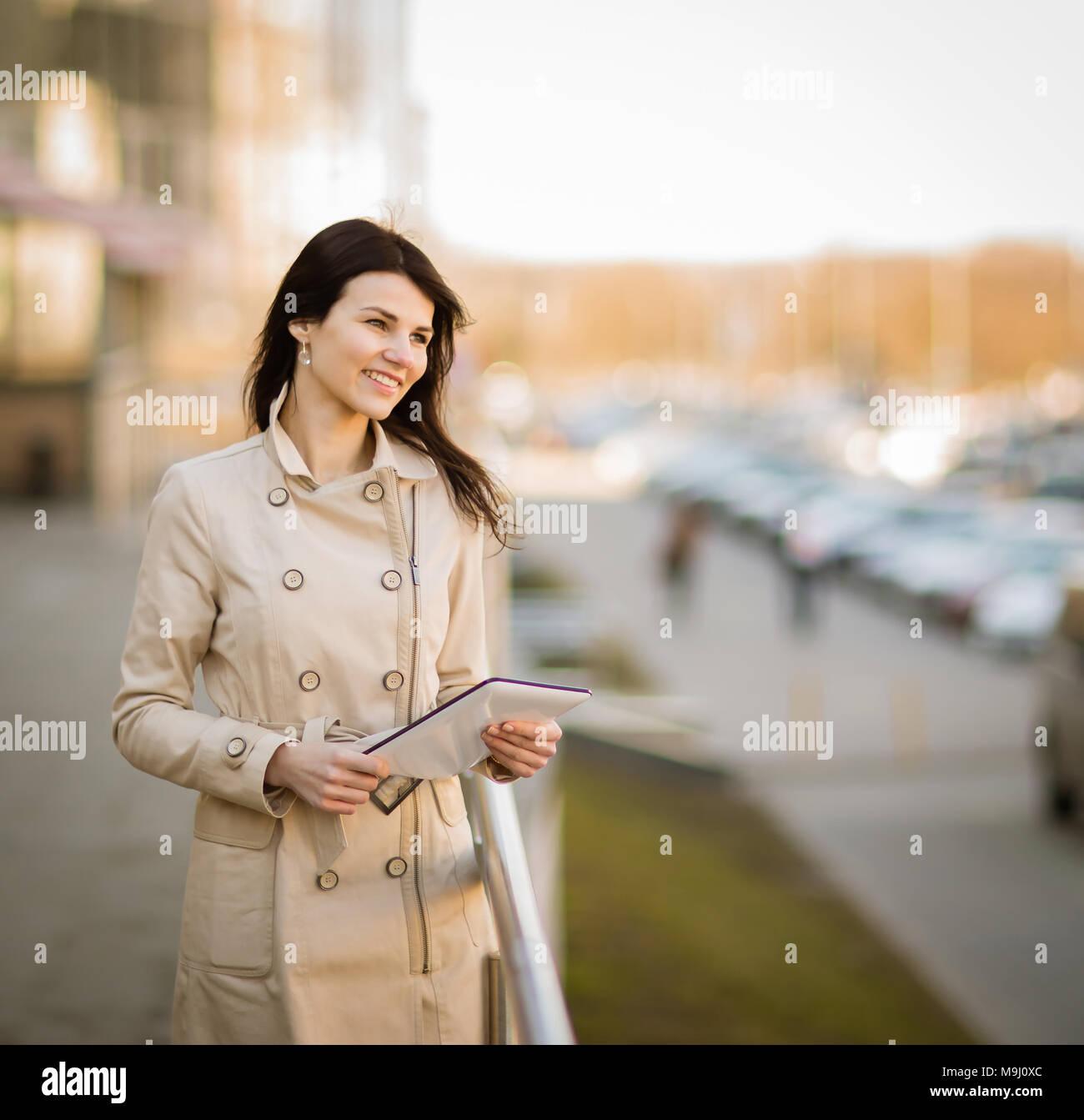 Die moderne Geschäftsfrau, die auf einem digitalen Tablet, neben einem Bürogebäude Stockbild