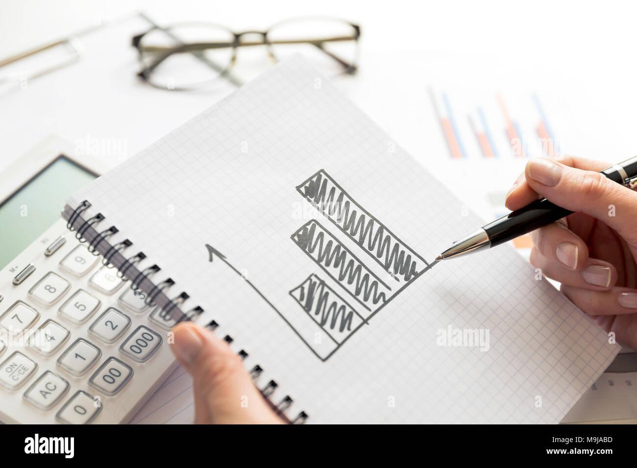 Geschäftsfrau, die am Projekt über das Wachstum der Unternehmen. Zeichnung eines wachsenden Grafik im Notebook Stockbild