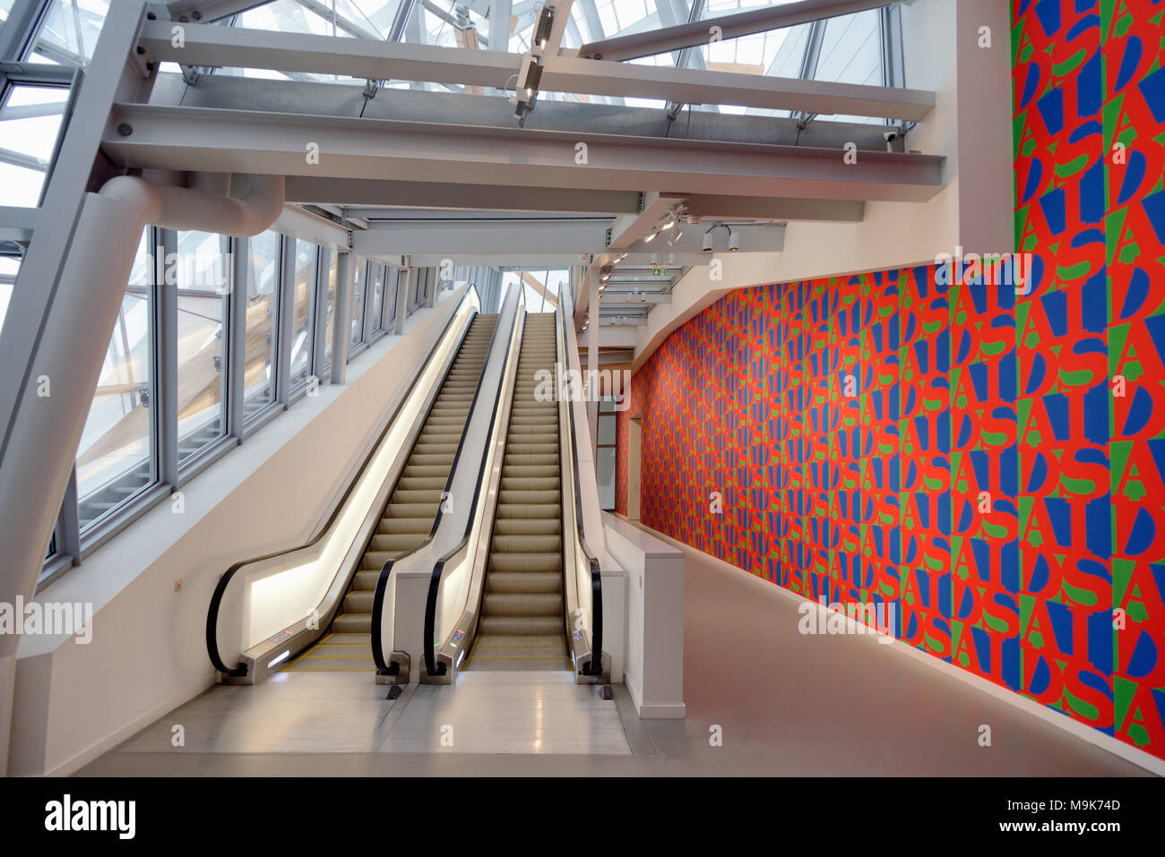 Fahrtreppen & Aids Tapete im Flur des Louis Vuitton Stiftung Kunst Museum & Cultural Center (2006-14.4.2006) von Frank Gehry entworfenen, Paris, Frankreich Stockbild