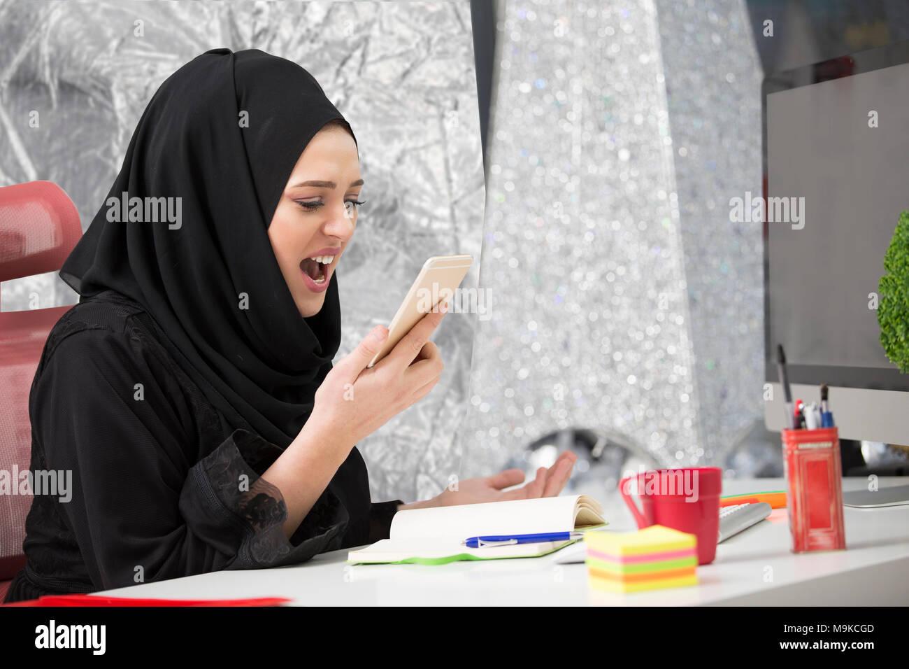 Muslimische Arbeitnehmerin, am Telefon zu sprechen während der Arbeit mit dem Laptop. Stockfoto