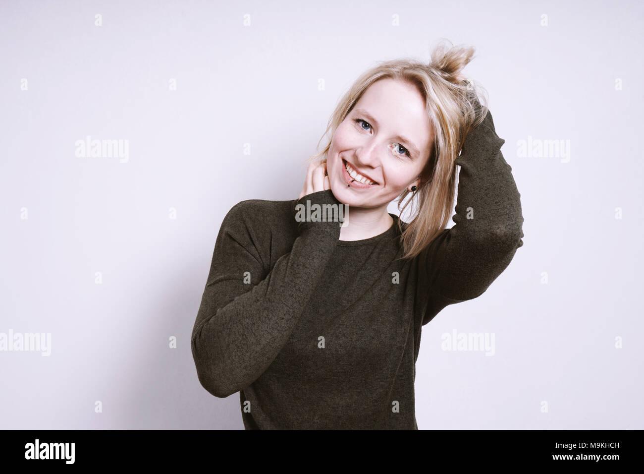 Glückliche junge lächelnde Frau mit Händen in Haar Stockbild