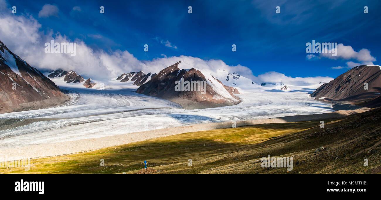 Blick auf verschneite Altai Gebirge mit Wolken und blauer Himmel, Mongolei Stockbild