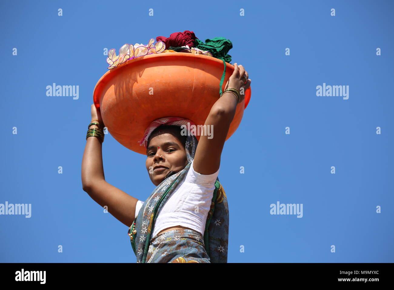 Indische Frau nach dem Waschen der Wäsche mit waschen Schüssel auf dem Kopf - Indische Frau / dem Wäsche waschen mit Waschschüssel mit dem Kopf Stockbild