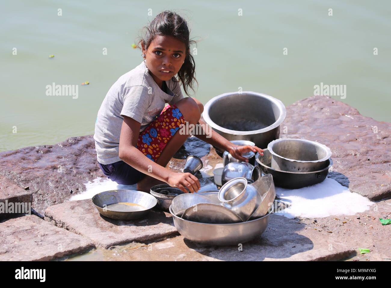 Indisches Mädchen Geschirr am Fluss - indisches Mädchen beim Gechirr Waschen am Fluss Stockbild