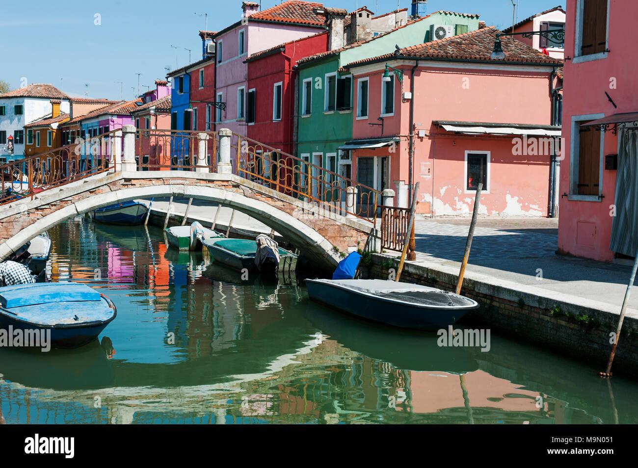 Insel Burano, Venedig, Italien - schöne Aussicht auf die Gracht, bunte Häuser, Boote und eine Brücke Stockbild