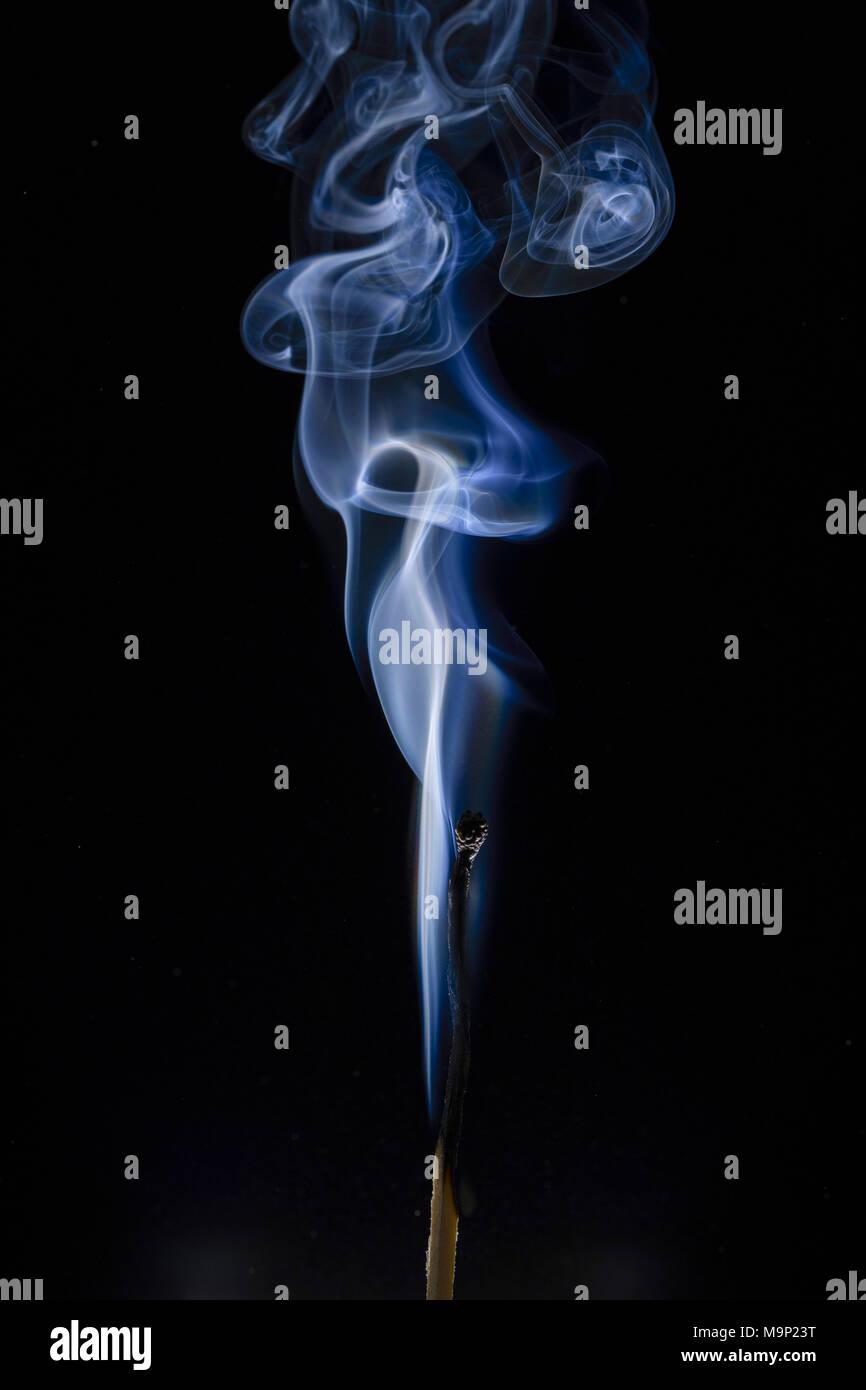 Gebrannt mit blauer Rauch vor einem dunklen Hintergrund, Studio shot Stockbild