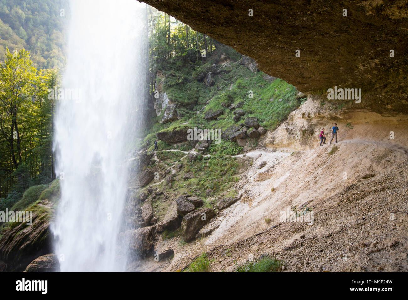 Zwei Menschen laufen über Trail hinter den Wasserfall Pericnik in alpine Vrata Tal in der Nähe von Mojstrana im Triglav Nationalpark, Slowenien Stockbild