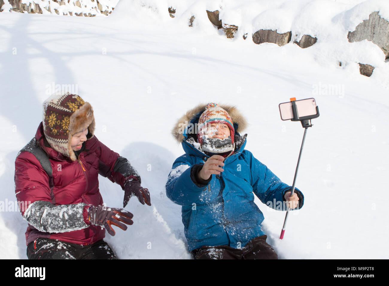 Ein junges Paar ist im Schnee spielen in Seoraksan Nationalpark, Gangwon-do, Südkorea. Das Mädchen warf nur einen Schneeball im Gesicht von ihrem Freund, der Filmen mit einem Smart Phone auf einem selfie stick ist. Seoraksan ist ein schönes und iconic National Park in den Bergen in der Nähe von Sokcho in der Region Gangwon-do in Südkorea. Der Name bezieht sich auf verschneite Felsen bergen. Satz gegen die Landschaft sind zwei Buddhistische Tempel: Sinheung-sa und Beakdam-sa. Diese Region ist Gastgeber der Olympischen Winterspiele im Februar 2018. Seoraksan ist ein schönes und iconic National Park in den Bergen in der Nähe von Sokcho im Stockbild