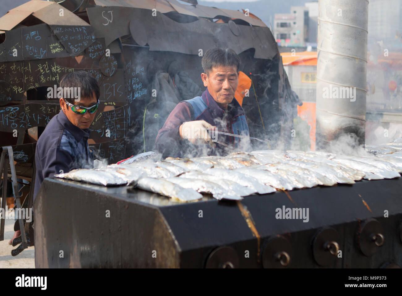 Ein Mann ist frisch gefangenen Fisch grillen am Hwacheon Sancheoneo Ice Festival. Die Hwacheon Sancheoneo Ice Festival ist eine Tradition für die Menschen in Korea. Jedes Jahr im Januar Menschenmassen versammeln sich auf dem zugefrorenen Fluss der Kälte und dem Schnee des Winters zu feiern. Hauptattraktion ist Eisfischen. Jung und Alt warten geduldig auf ein kleines Loch im Eis für eine Forelle zu beißen. In zelten Sie können den Fisch vom Grill, nach dem sie gegessen werden. Unter anderem sind Rodeln und Eislaufen. Die in der Nähe Pyeongchang Region wird Gastgeber der Olympischen Winterspiele im Februar 2018. Stockbild