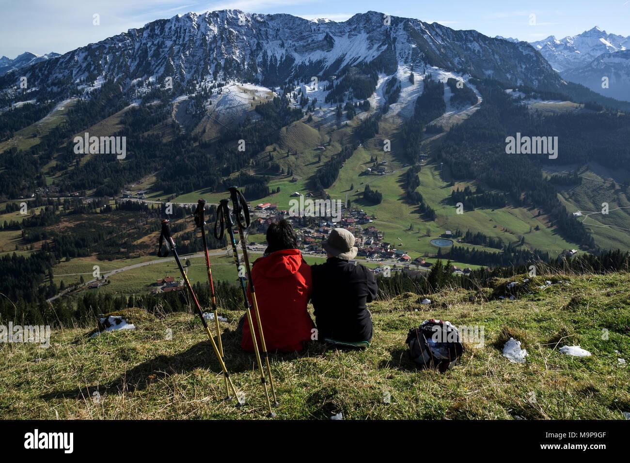 Zwei Wanderer sitzen im Gras und der Blick auf und die iseler Oberjoch, Oberjoch, Allgäu, Bayern, Deutschland genießen Stockbild