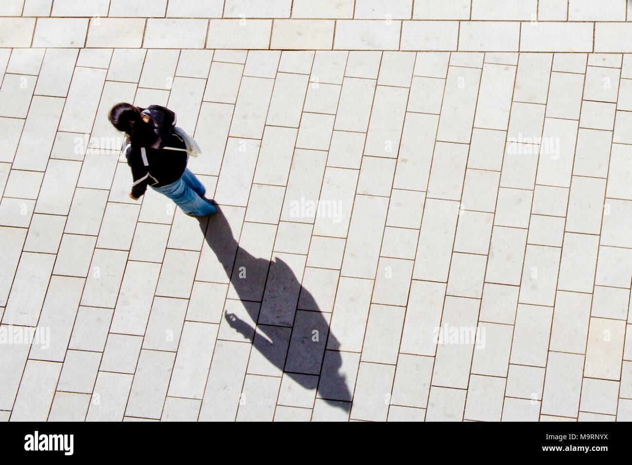 Frau gehen auf die Straße und die langen Schatten projiziert, Ansicht von oben Stockbild