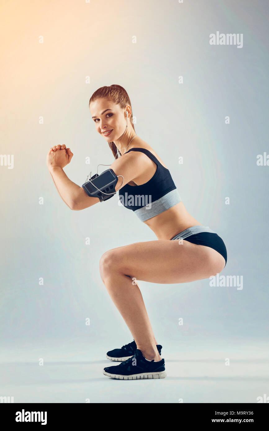 Freudige junge weibliche Athleten tun Hocke übung und lächelnd Stockbild