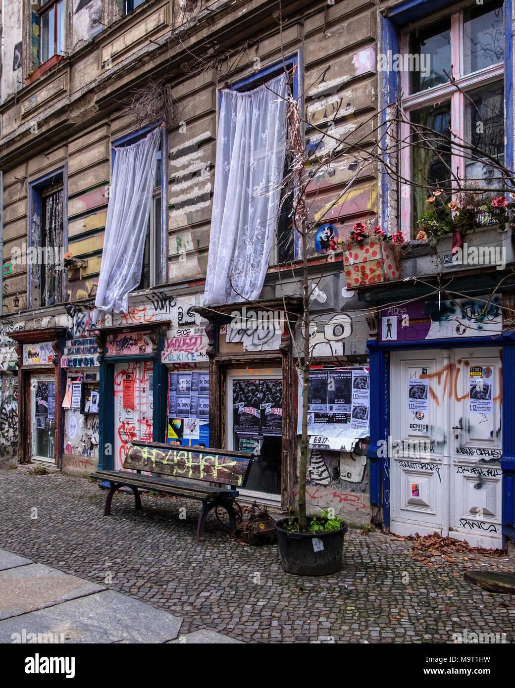 Berlin, Prenzlauerberg, KA-86. Fassade des ehemaligen verfallenen niedriges Gebäude mit Plakaten und Vorhänge vor dem Fenster hängen, Schrulligen äußere Verzierung Stockbild