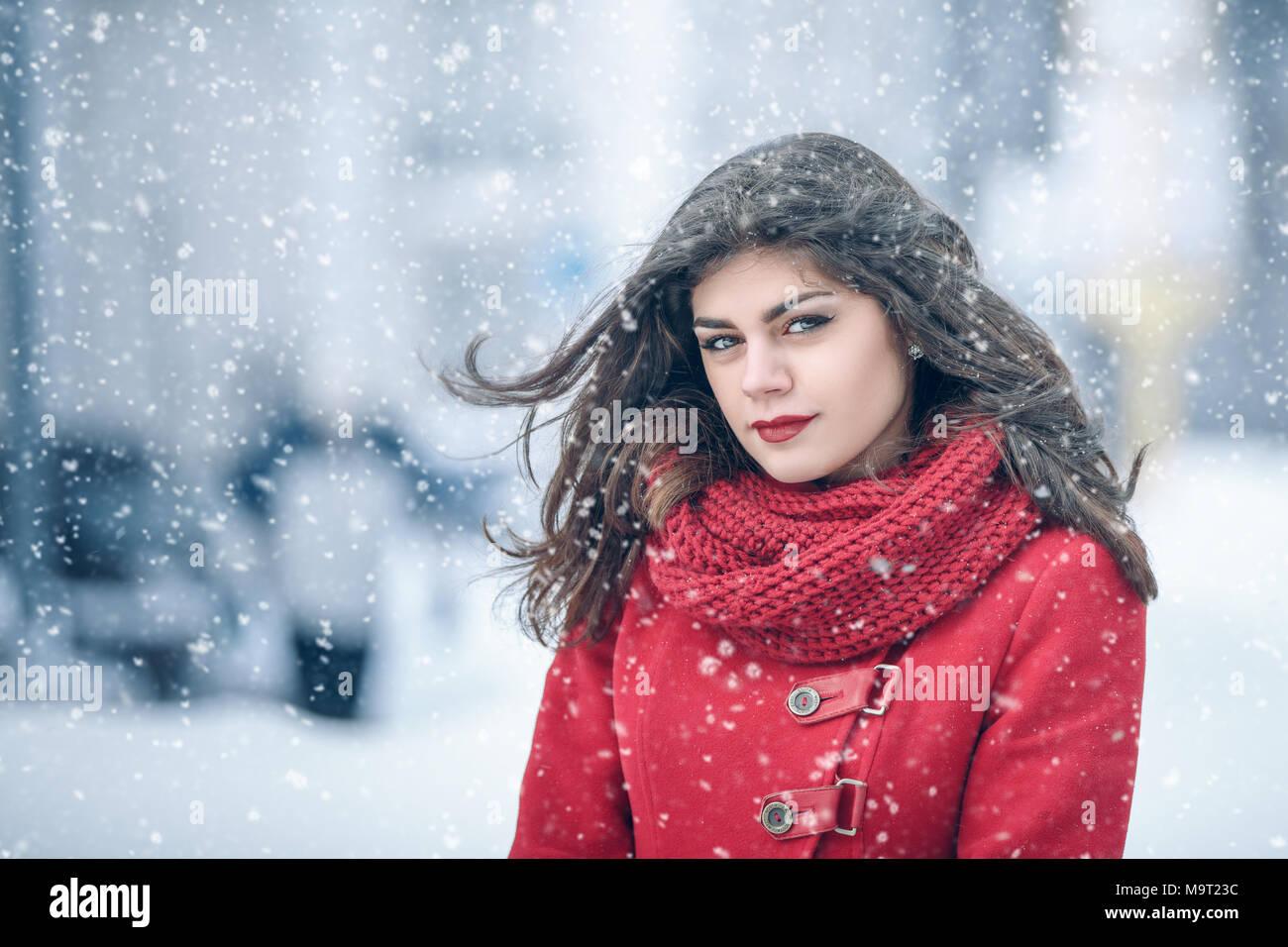 Winter. Mädchen brunette capless Lächeln auf dem Hintergrund der Schnee. Close-up. Haar entwickelt. Wind und Schnee Stockfoto