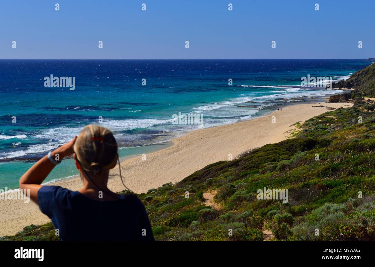 Frau auf der Suche nach Norden entlang Yallingup Strand in Richtung Cape Naturaliste Lighthouse, Surakarta, Western Australia Stockbild