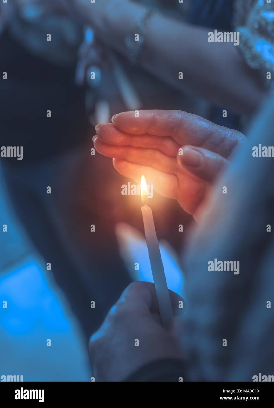 Gläubiger in einer Kirche mit Kerze, Nahaufnahme einer Frau deckt die Flamme der Kerze mit ihrer Hand, bittet um Hilfe von Gott auf den Osterferien Stockfoto