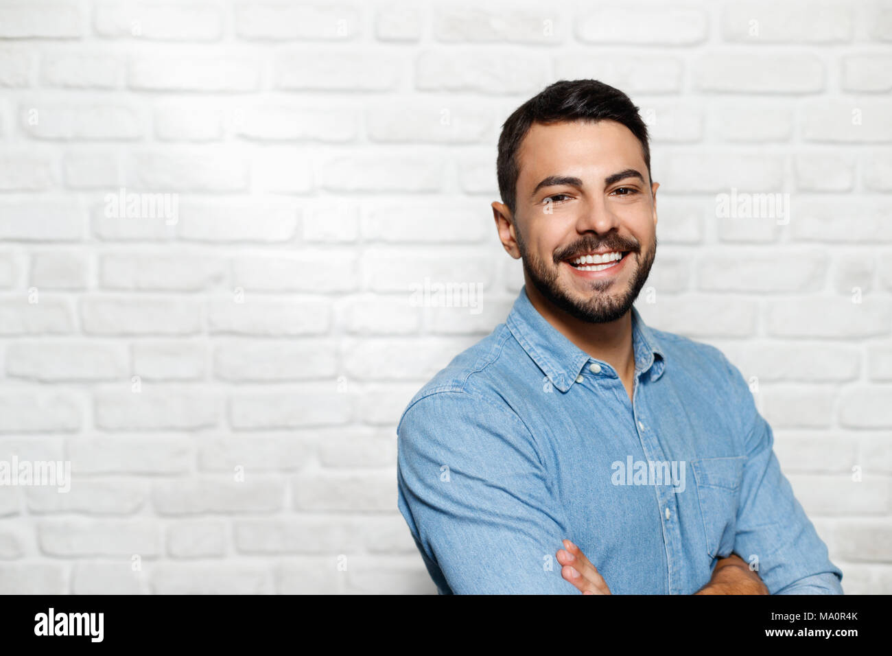 Portrait von glücklichen italienischen Mann lächelnd gegen weiße Wand als Hintergrund und Kamera. Stockbild