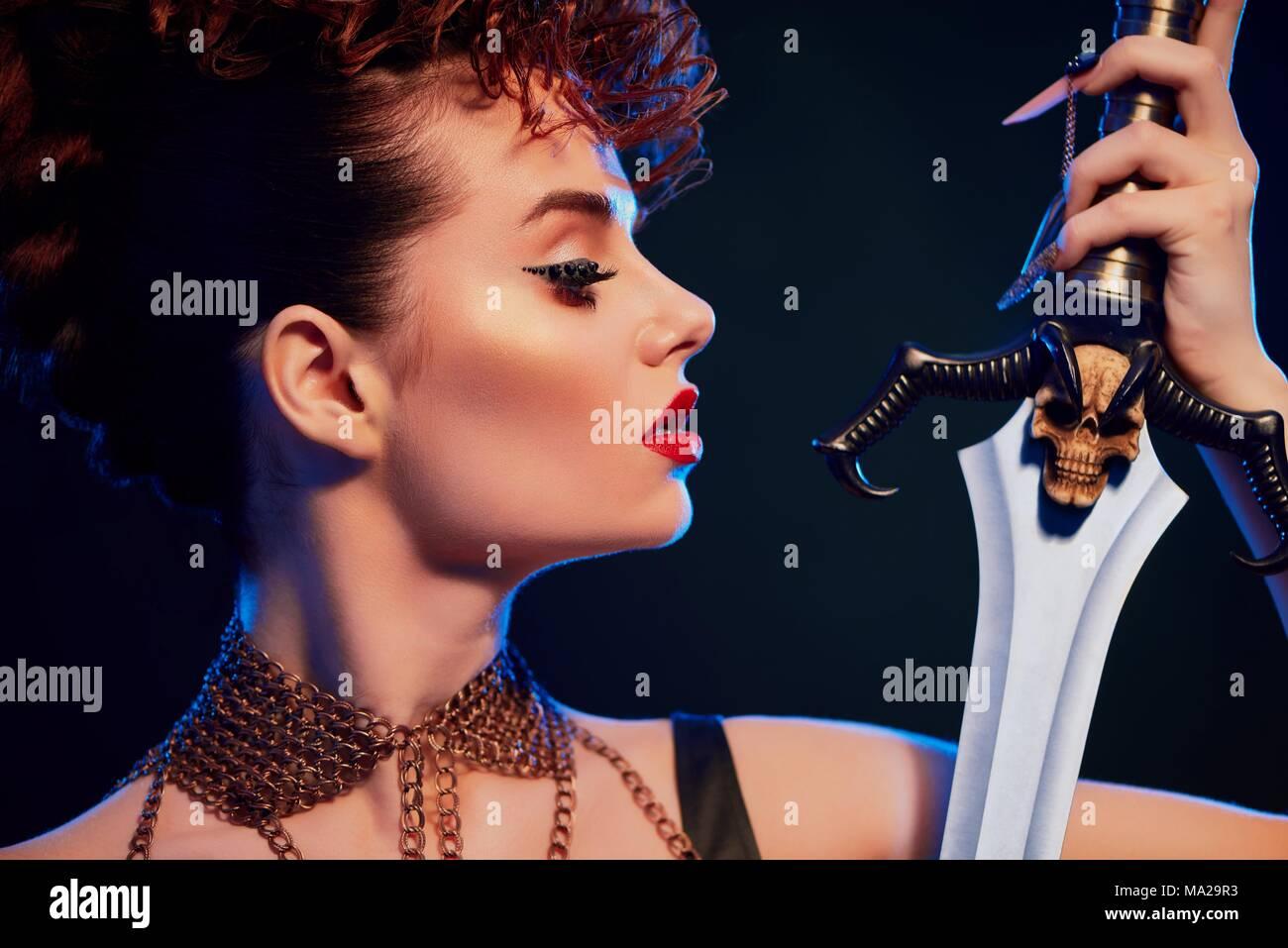 Junge schöne Mädchen mit hellen Erscheinungsbild das Tragen der roten Lippenstift und original Frisur ist auf der Suche nach Stahl Schwert mit schwarzen Schädel. Das Modell trägt schwarz Top mit schmalen Ketten mit kleine Kreuze auf dem Hals. Stockbild