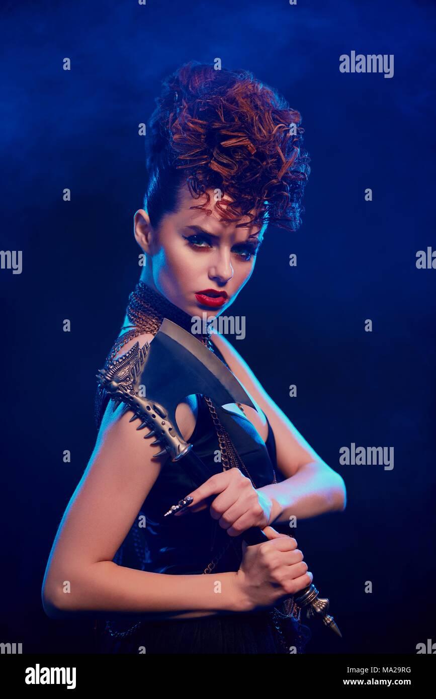 Seitenansicht des phantastischen Mädchen halten scharfe Metallische ax mit Dornen. Weibliche Krieger stehen auf dunkelblau smoky Hintergrund. Modell mit schwarzen top mit geöffneten Schultern, Make-up und stilvolle hairdress. Stockbild