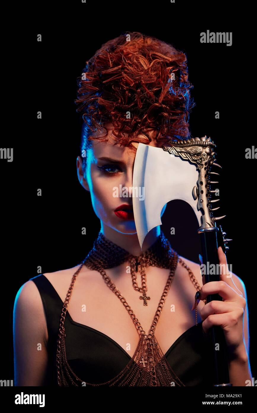 Portrait von Mädchen halten Original scharfe Metallische ax mit Dornen. Zuversichtlich Modell tragen in Schwarz mit geöffneten Schultern, mit Make-up und Curly hairdress. Ketten mit Kreuzen auf den Hals der Frau. Stockbild
