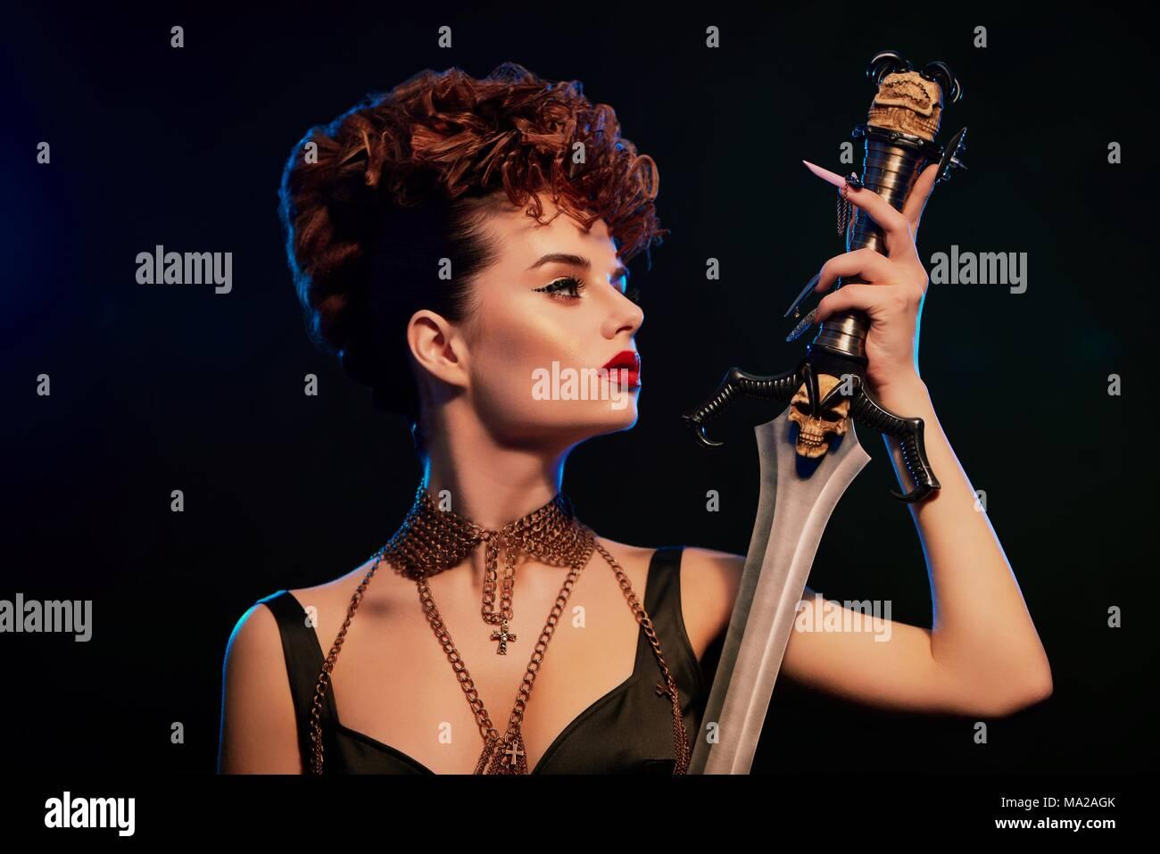 Modische junge Modell mit hellen Stellen halten Stahl Schwert mit schwarzen Schädel. Frau mit stilvollen hairdress mit wenig curles. Frauen in Schwarz top mit schmalen Ketten. Zuversichtlich original. Stockbild