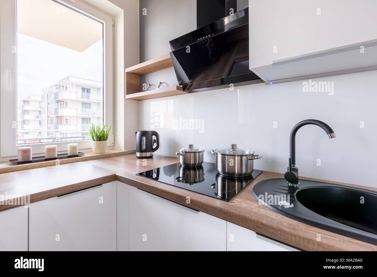 Moderne, weiße Küche mit Spüle, Arbeitsplatte und Fenster aus Holz ...