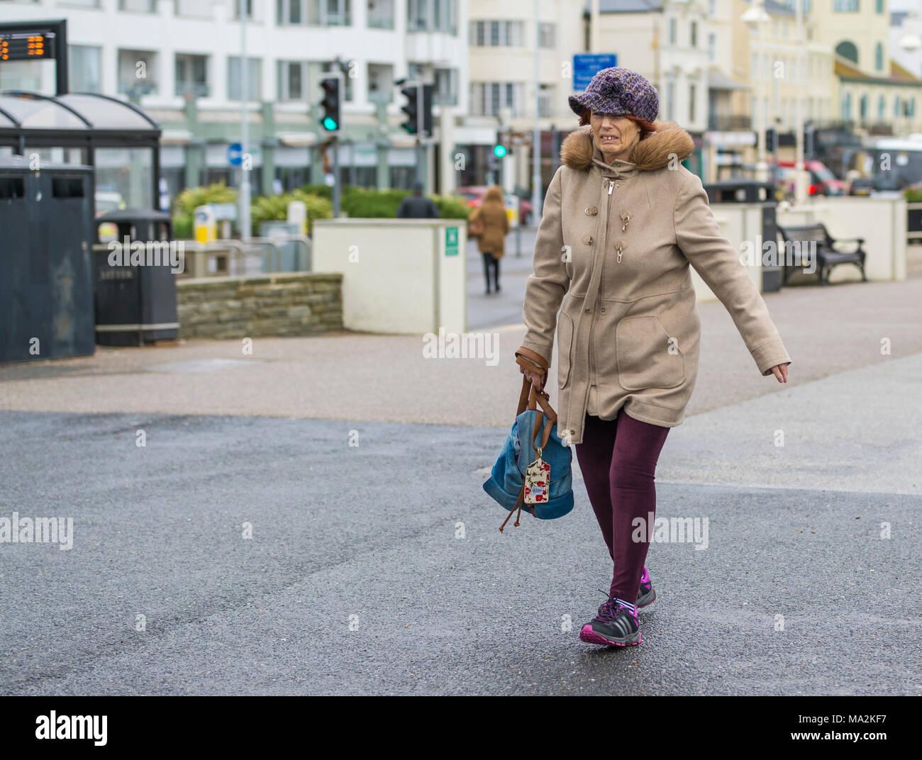Aktive ältere Dame in einen dicken Mantel und Hut mit Tasche das schnelle Gehen bei kaltem Wetter gekleidet. Stockbild