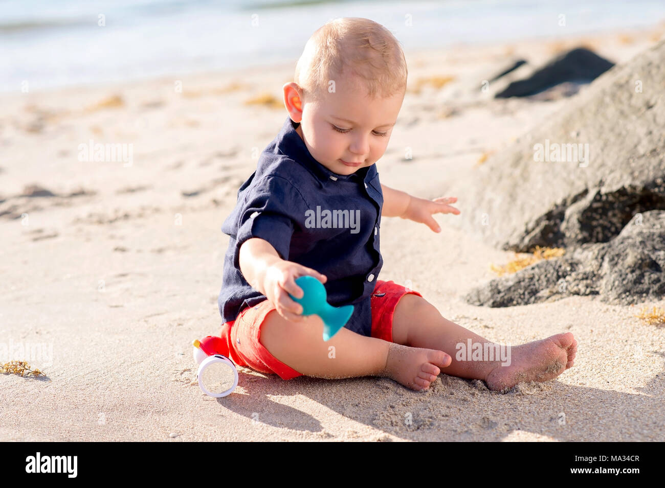 ein 1 jahr altes baby junge sitzt auf einem strand und spielen mit einem spielzeug stockfoto. Black Bedroom Furniture Sets. Home Design Ideas