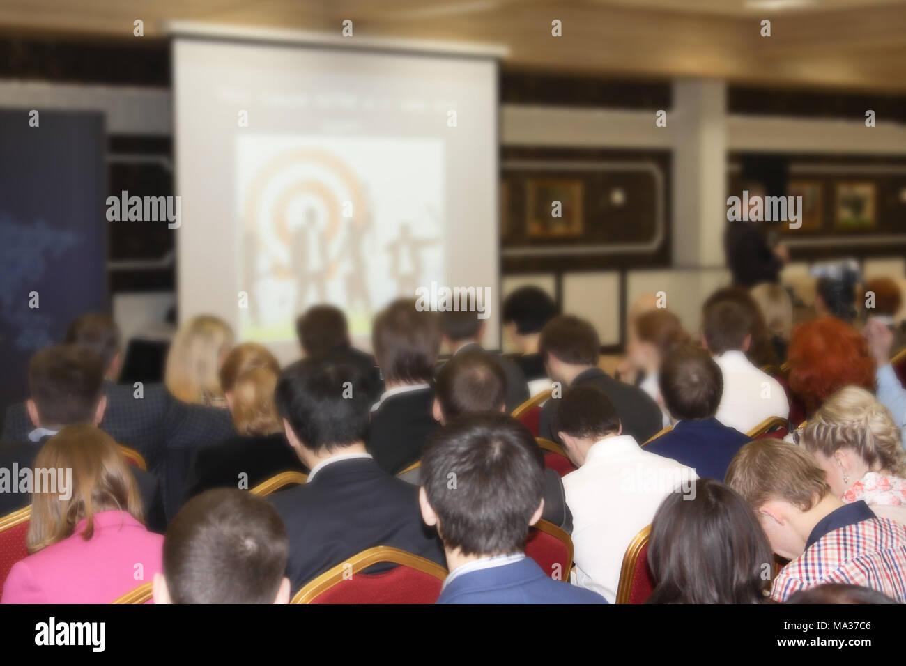In einer riesigen Halle eine große Anzahl von Personen, die geschult sind, ein Seminar über neue Arten des Geschäfts Stockbild