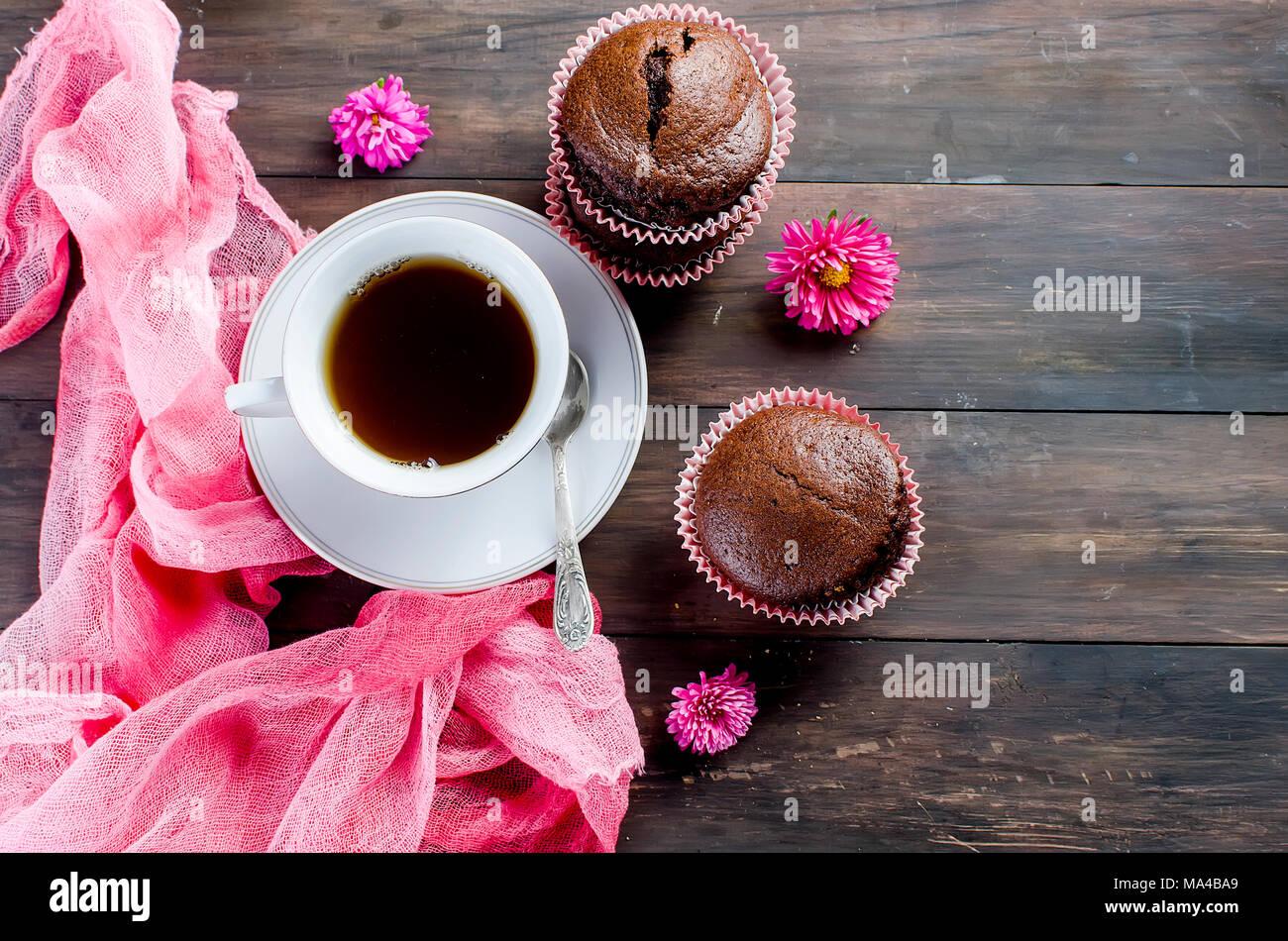 Chocolate Muffins und eine Tasse Kaffee Frühstück noch Leben auf einem dunklen Holztisch. Platz kopieren, Ansicht von oben. Stockbild