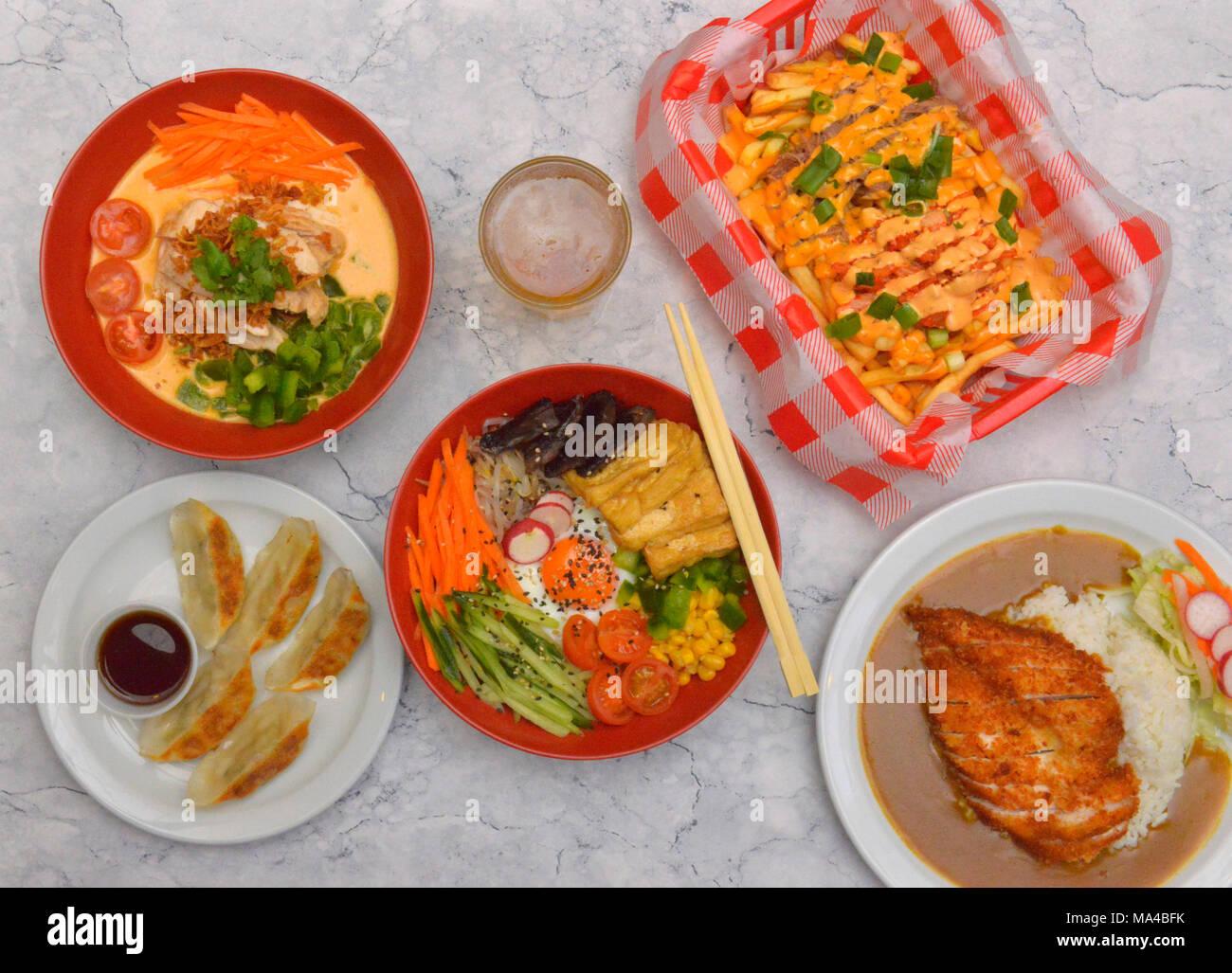 Eine Auswahl von koreanischen Speisen wie Tofu & Pilz Kimchi bimbimbap, Rindfleisch, Hähnchen Red Curry, Gemüse Knödel, knusprige panko Huhn Katsu Curry. Stockbild