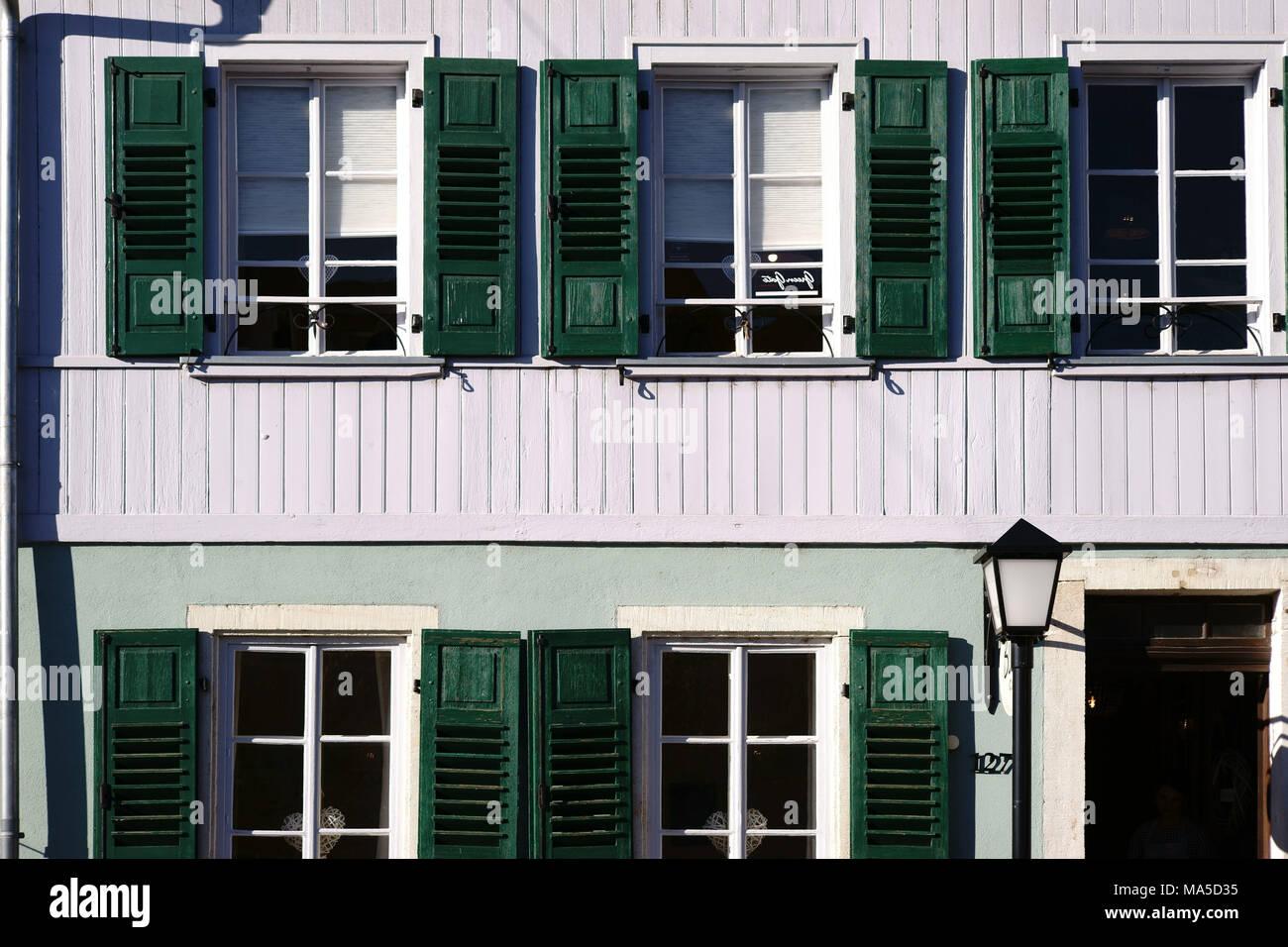 Reihenhaus mit nostalgischen Fensterläden aus Holz und einer Laterne, Stockbild