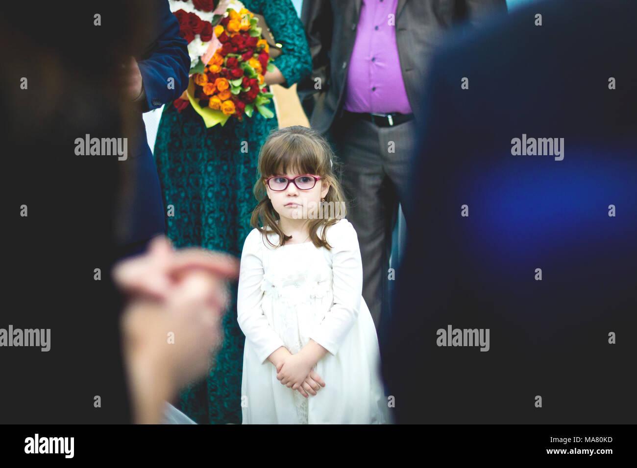 Traurige kleine Mädchen in weißem Kleid in der Menge bei der ...
