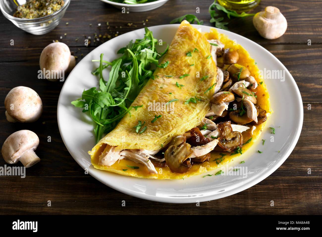 Nahaufnahme von Omelett mit Champignons, Hühnerfleisch, Grüns auf Holztisch. Gesunde Lebensmittel für Frühstück. Stockbild