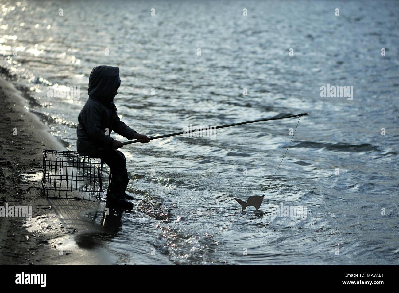 Ein fünf Jahre alter Junge ist das Angeln am See. Stockbild