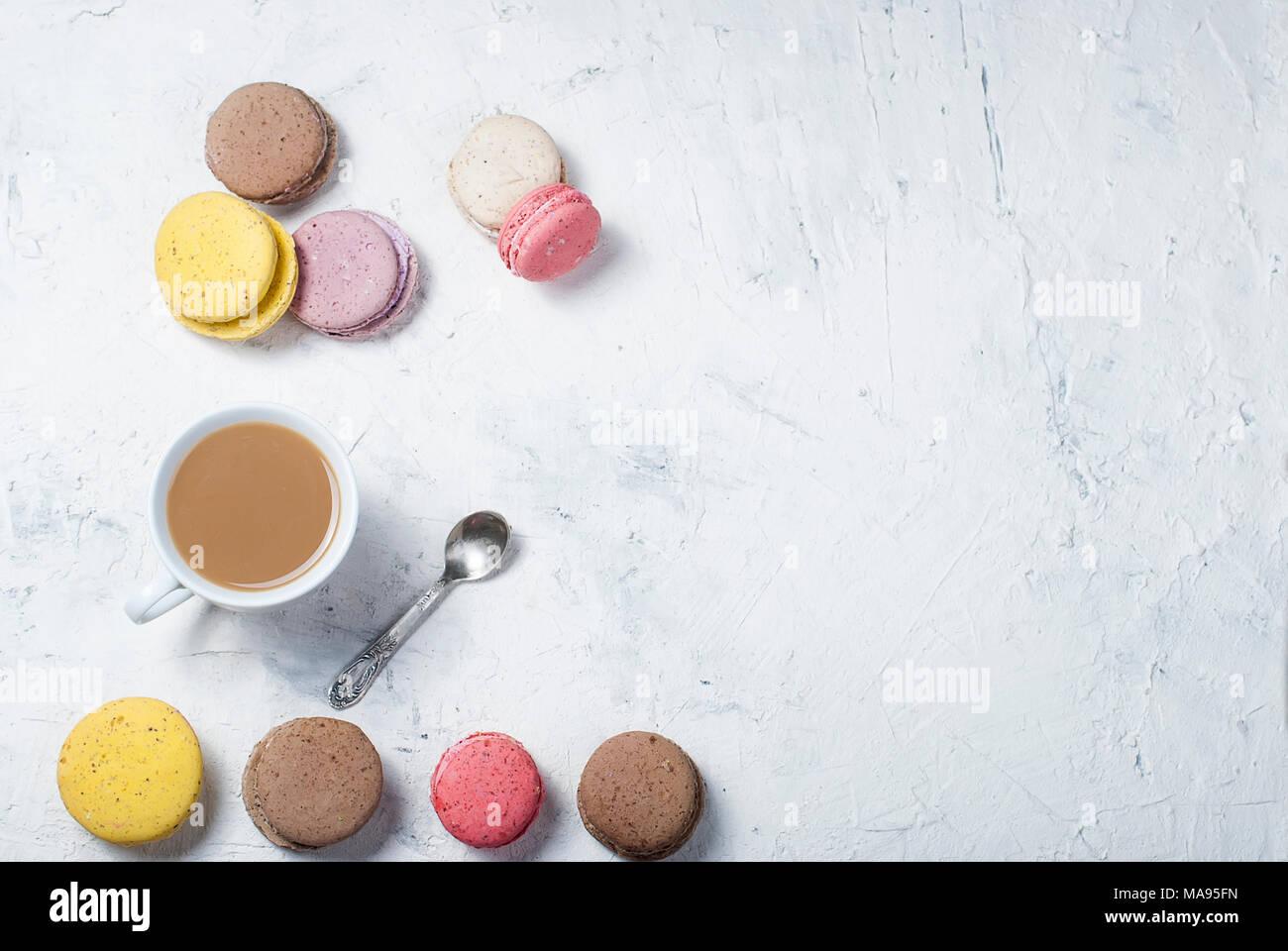 Tasse Kaffee mit Milch und bunten makaoouns auf einem hellen Hintergrund. Ansicht von oben. Kopieren Sie Platz. Stockbild