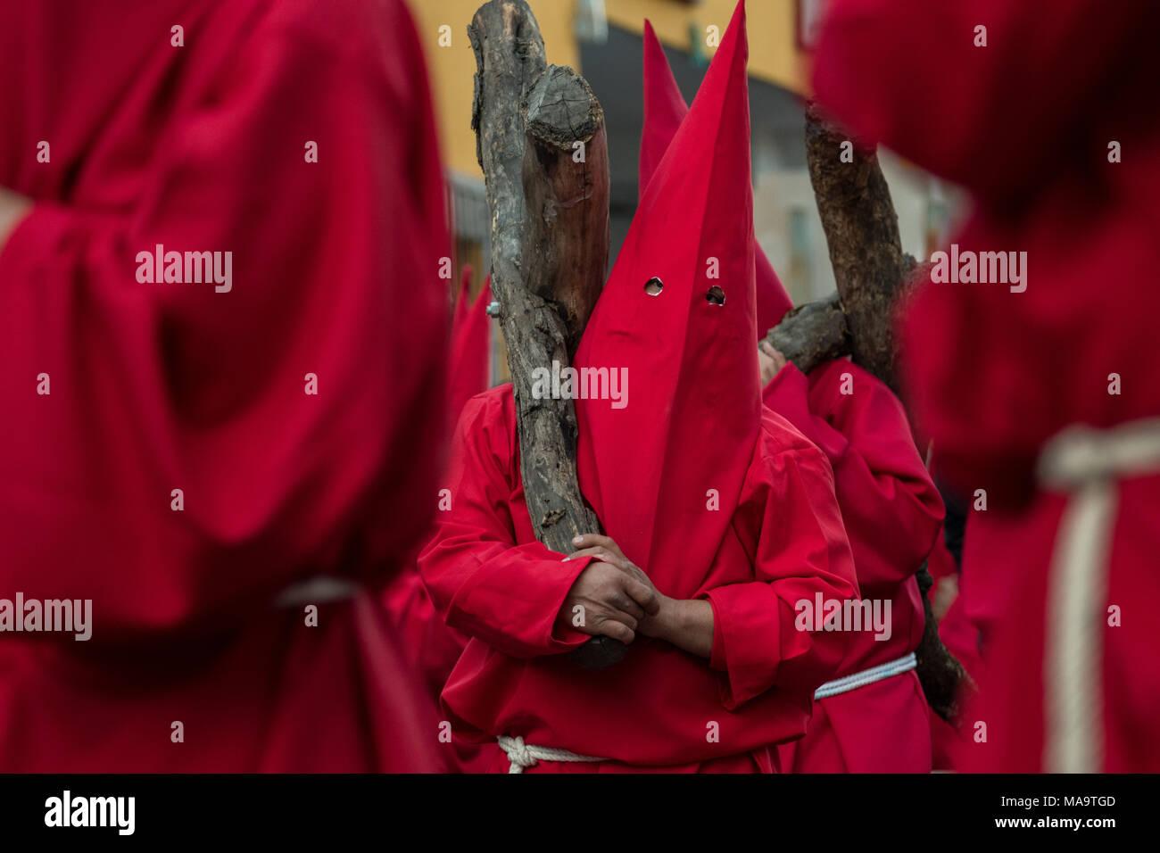 Querétaro, Mexiko, 31. Feb 2018. Vermummte Büßer tragen eine schwere hölzerne Kreuze durch die Straßen der Stadt während der Prozession der Stille als Teil der Heiligen Woche März 30, 2018 in Querétaro, Mexiko. Die Büßer, bekannt als Nazarener, schwer tragen, Kreuze und Ketten ziehen an einem vierstündigen März den Schmerz zu erstellen und Leidens während der Passion Christi. Credit: Planetpix/Alamy leben Nachrichten Stockfoto