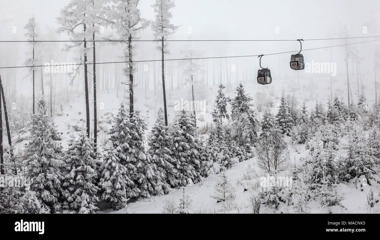 Zwei Sessellift Kabinen jeder sonstigen Weitergabe grauen Winter bewölkten Tag. Skigebiet Tatranska Lomnica, Slowakei Stockbild