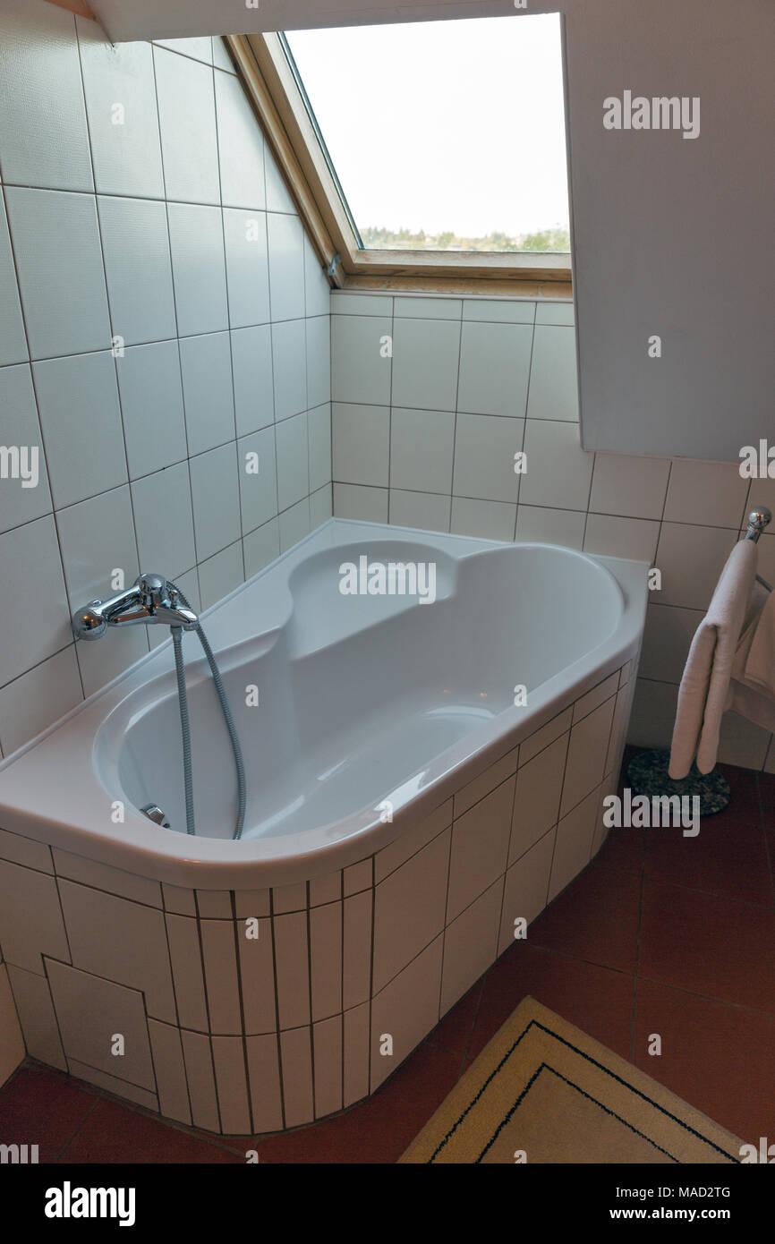 Modernes weißes, kleines Bad mit Eckbadewanne, Handtücher ...