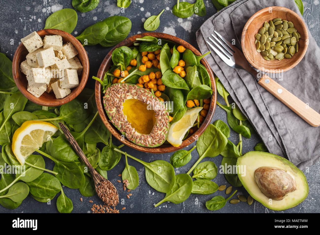 Gesunde vegetarische Salat mit Tofu, Kichererbsen, Avocado und Sonnenblumenkernen. Gesunde vegane Ernährung Konzept. Dunkler Hintergrund, Ansicht von oben, kopieren. Stockbild