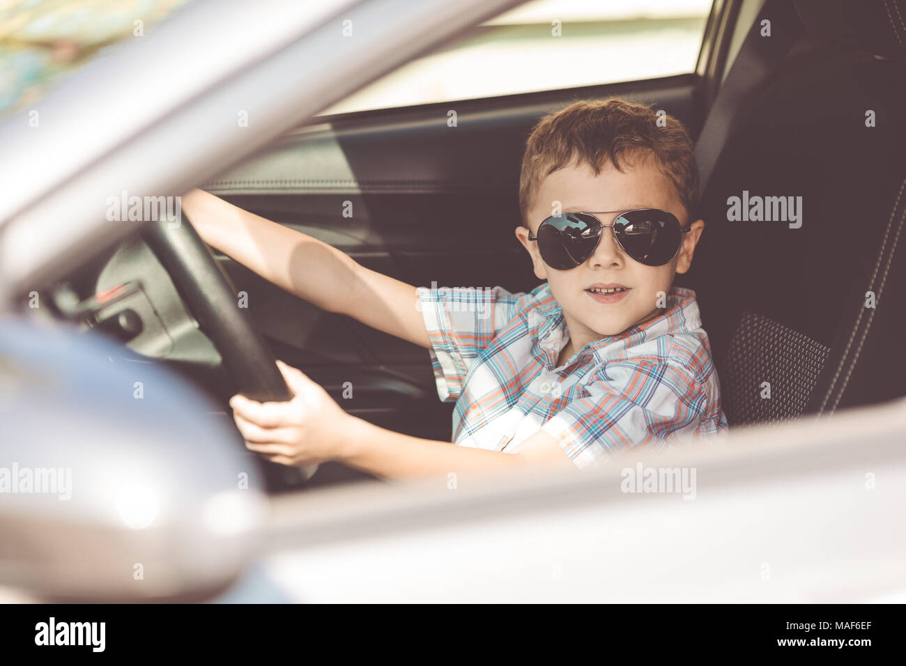 Ein kleiner Junge sitzt im Auto am Tag Zeit glücklich. Konzept der Sommerferien. Stockbild