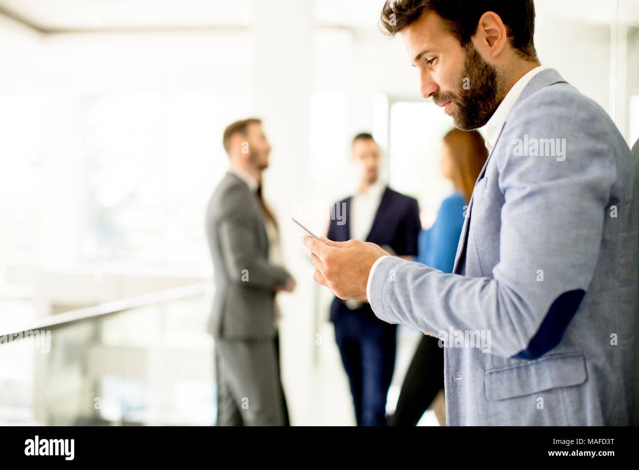 Hübscher junger Geschäftsmann mit Mobiltelefon im Büro Stockbild