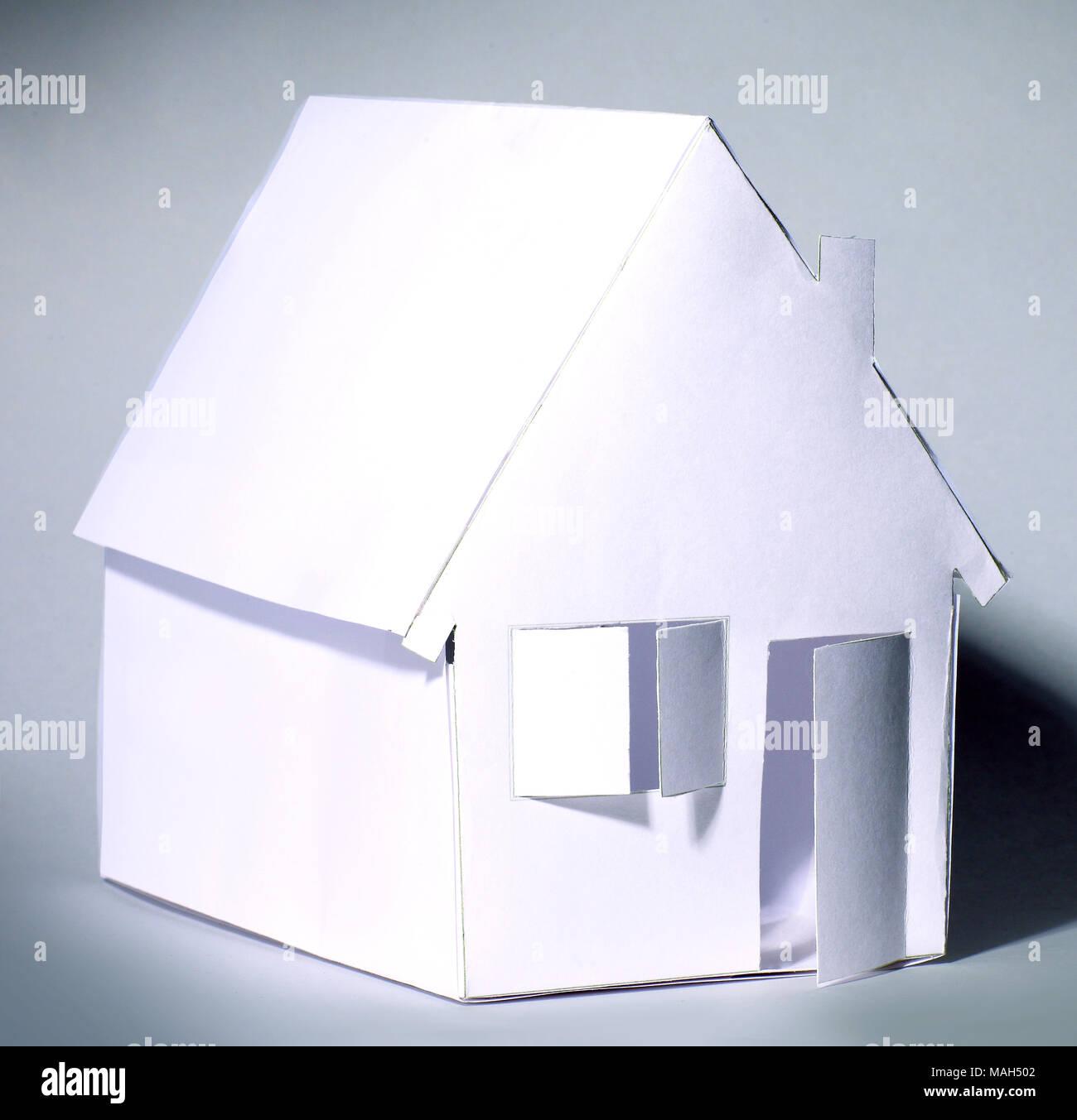 Papier Haus mit offener Tür. Isolierte auf Grau Stockbild