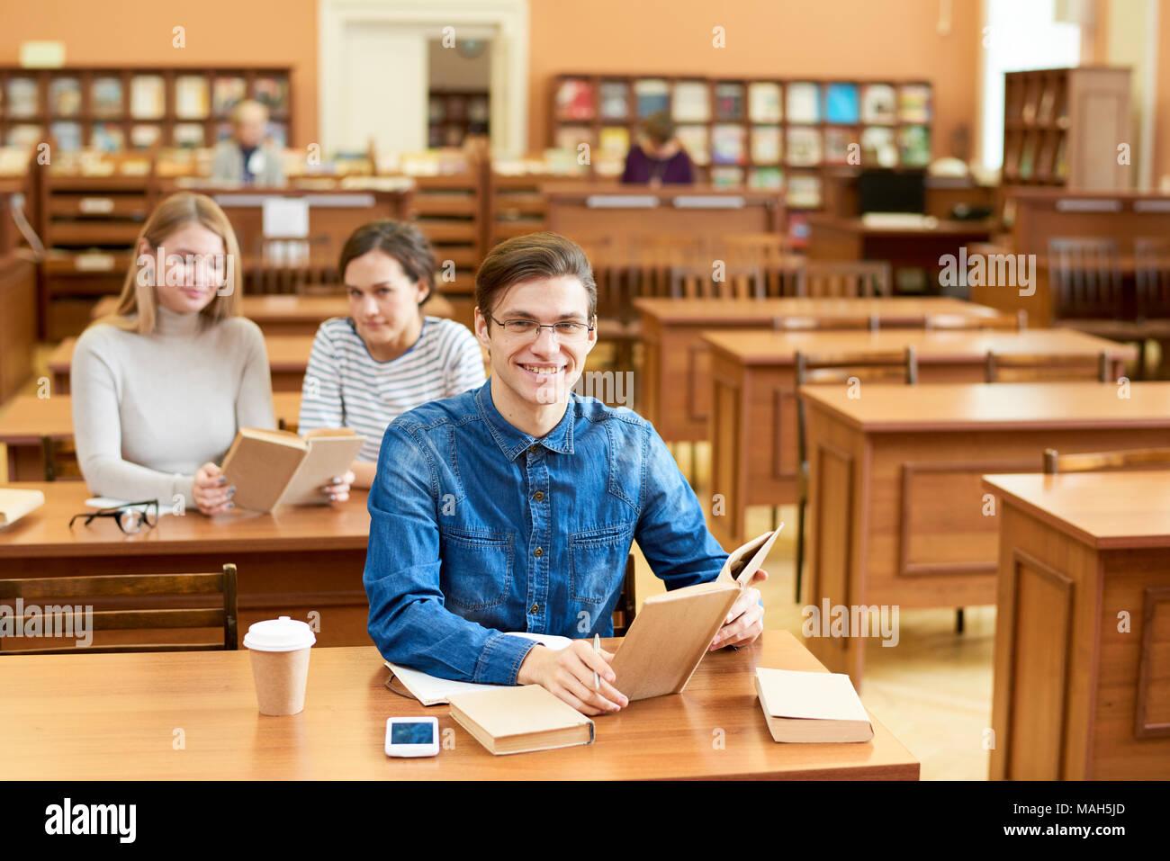 Aufgeregt fleissiger Student in Bibliothek Stockbild