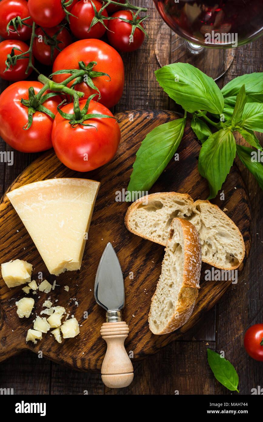 Parmesan, Ciabatta, Basilikum, frischen Tomaten und Glas Rotwein. Italienische Küche, italienische Küche. Ansicht von oben Stockbild